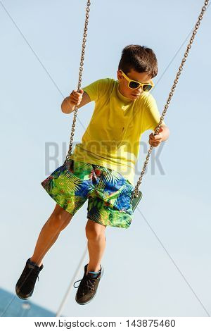 Boy Playing Swinging By Swing-set.