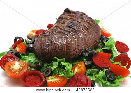 fresh ripe roasted big chunk of beef meat on green salad with tomatoes isolated on white