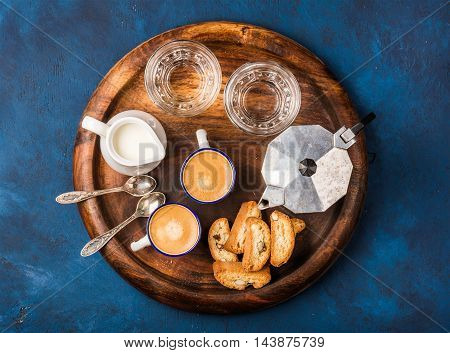 Coffee espresso in cups with italian cantucci, cookies and milk in jug on wooden serving round board over dark blue painted plywood background, top view, horizontal composition
