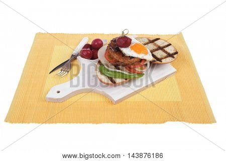 junk food meat big beef hamburger fried eggs on white wood plate with cutlery ketchup sauce and pickles on yellow mat isolated over white background