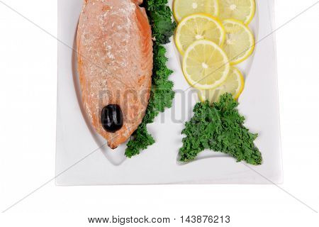 healthy food - fresh roast red fish salmon with kale lemon and black olives on plate isolated on white background space for text