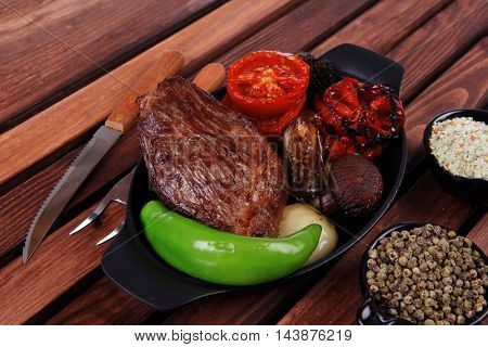 fresh roast bbq beef steak on black pan baked with mushroom potatoes tomatoes green hot chili pepper served with different peppercorn on dark wooden table