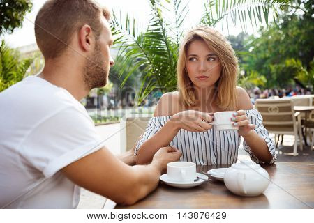 Young beautiful couple drinking tea, speaking, quarreling, sitting in cafe
