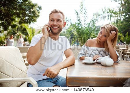 Young beautiful couple sitting in cafe. Man speaking on phone while his girlfriend being bored.
