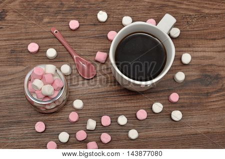 A mug and a jar filled with small marshmallows and a little pink teaspoon