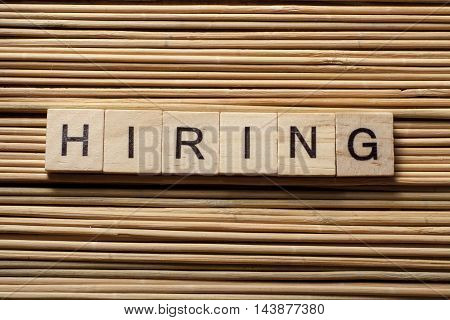 HIRING word written on wood block. Wooden Abc.