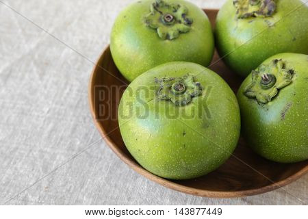 Sapote or black chocolate pudding fruit in wooden bowl