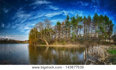 Sunny day on a calm river in summer. Dramatic blue sky