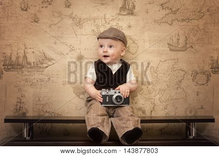 the funny baby traveler is sitting with a retro camera