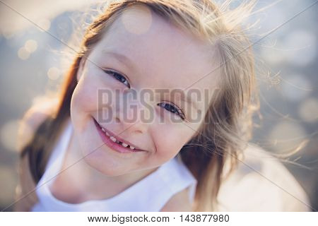 Happy little girl smiling soft focus fairy light toning background