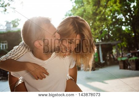 Young beautiful couple smiling, kissing, rejoicing, embracing walking in park