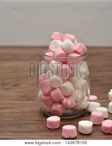 A bottle filled with small pink and white marshmallows