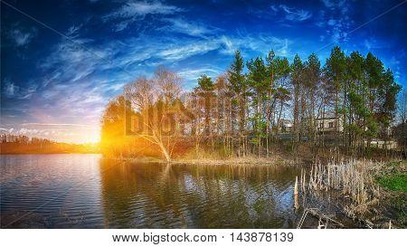 Sunset over the lake in the village. Dramatic blue sky