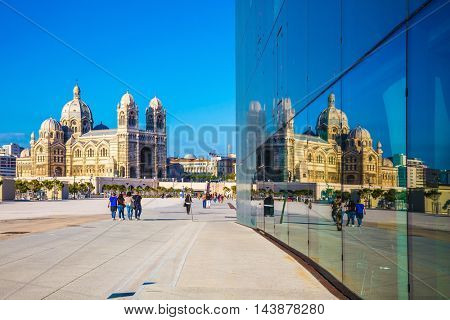 MARSEILLE, FRANCE - MAY 22, 2015: Cathedral of Saint Mary Major is reflected in the mirrored wall of a building on the waterfront of Marseille. Sunny spring morning