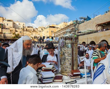 JERUSALEM, ISRAEL - OCTOBER 12, 2014: Jews for ritual tallit worship with prayer books in their hands. Imposition of a Torah scroll for prayer