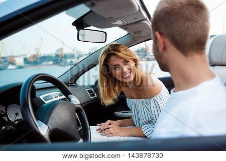 Young beautiful couple smiling, speaking, sitting in car near sea.