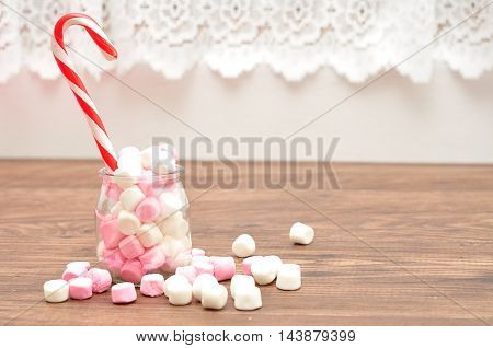 A candy cane in a jar filled with small pink and white marshmallows with a white background