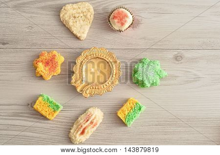 A golden Diwali candle with colorful biscuits