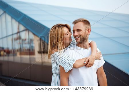 Young beautiful couple smiling, rejoicing, embracing, walking around city