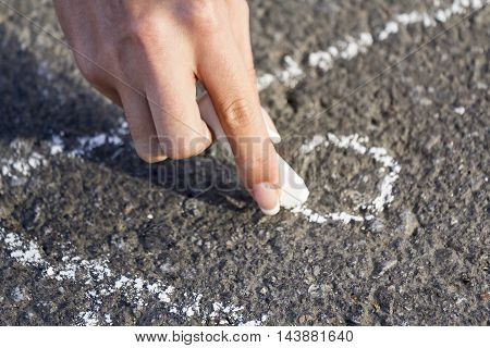 Hand girl draws by a chalk roof House on the sidewalk