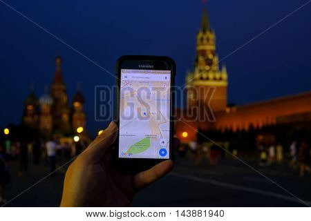 Moscow, Russia - July 31: Male hand holding a smartphone with a running Google maps app on the background of Red Square landmarks