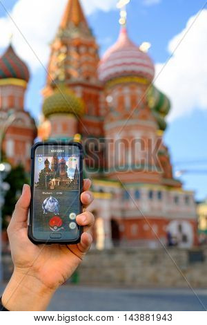 Moscow, Russia - July 31: Male hand holding a Samsung smartphone with a running modern augmented reality game Pokemon Go on the background of Red Square landmarks