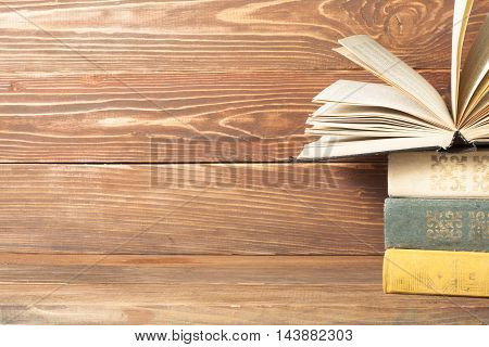 Open book, hardback books on wooden table. Education background. Back to school. Copy space for text