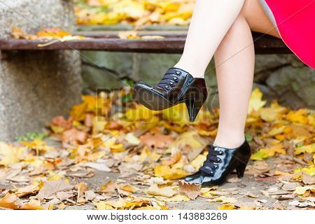 Leisure outdoor relax walk nature footwear shoes concept. Lady sitting on bench. Elegant female body part in park.