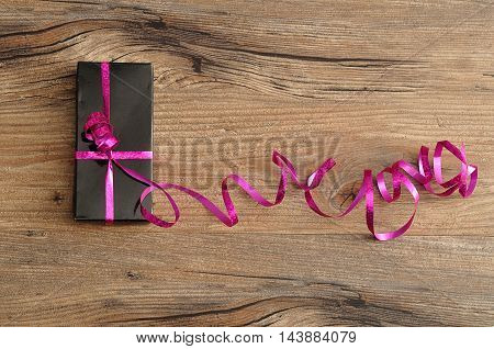 A black gift box decorated with a pink ribbon isolated on a wooden background
