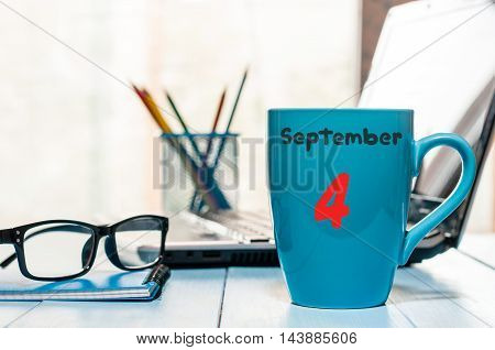 September 4th. Day 4 of month, wooden color calendar on student workplace background. Autumn time.