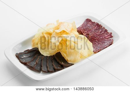 Sliced beef and pork bacon meat with fried potatoes on white plate