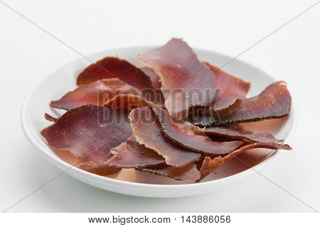 Sliced dried beef meat jerky on white plate