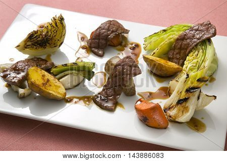 Beef roasted with vegetables cabbage sweet potato lotus and carrot on white plate