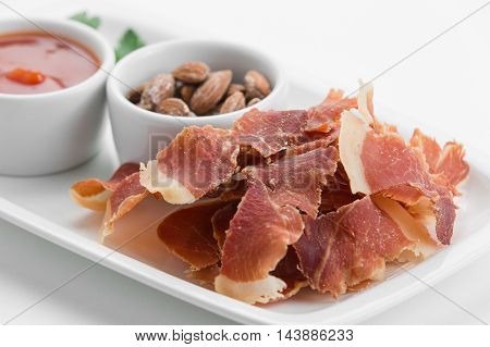 Spicy potato chips of ham with smoked almonds on white plate