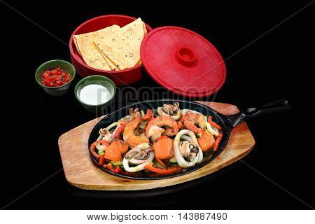 Mexican dishes with shrimp squid salmon and bread on black background
