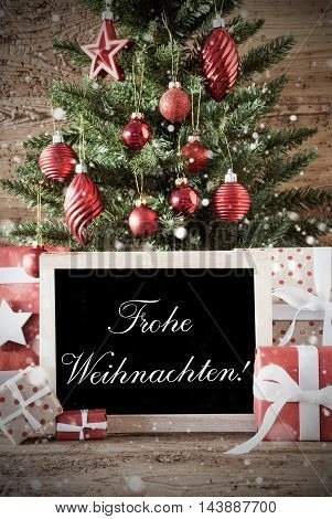 Nostalgic Christmas Card For Seasons Greetings. Christmas Tree With Balls. Gifts Or Presents In The Front Of Wooden Background. Chalkboard With German Text Frohe Weihnachten Means Merry Christmas