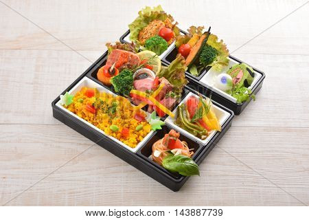 Bento meal of rice salmon broccoli lettuce and noodle on wooden table