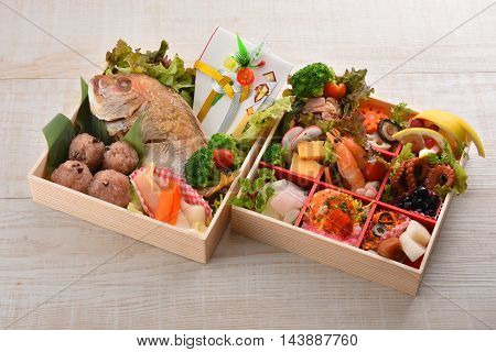 Bento box gift of dried seafood with snapper shrimp octopus mushroom broccoli lemon and rice ball on wooden table