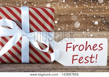 Christmas Gift Or Present On Wooden Background With Snowflakes. Card For Seasons Greetings. White Ribbon With Bow. German Text Frohes Fest Means Merry Christmas