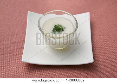 Rice soup in glass on white plate in restaurant