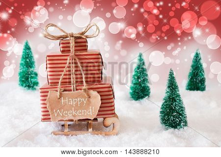 Sleigh Or Sled With Christmas Gifts Or Presents. Snowy Scenery With Snow And Trees. Red Sparkling Background With Bokeh Effect. Label With English Text Happy Weekend