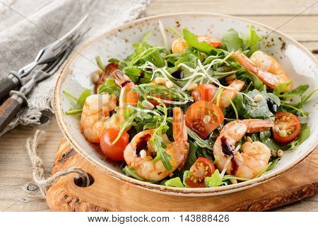 Rocket salad with prawns shrimps sprouts and green cabbage on wooden cutting board