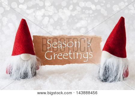Christmas Greeting Card With Two Red Gnomes. Sparkling Bokeh Background With Snow. English Text Seasons Greetings