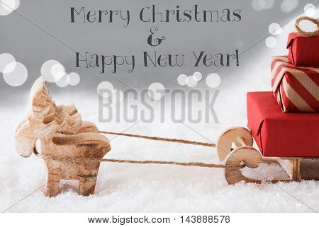 Moose Is Drawing A Sled With Red Gifts Or Presents In Snow. Christmas Card For Seasons Greetings. Silver Background With Bokeh Effect. English Text Merry Christmas And Happy New Year