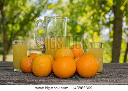 delicious orange juice and oranges on table in garden