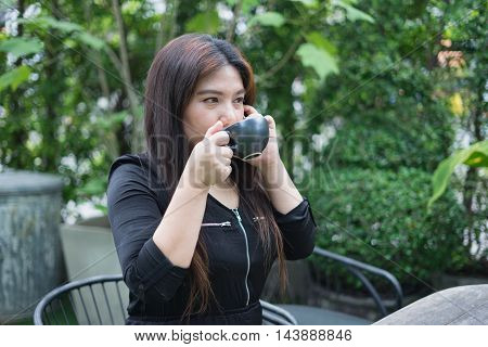 woman is sipping hot coffee at coffee time at park or garden with mobile phone on her hand and relax atmosphere