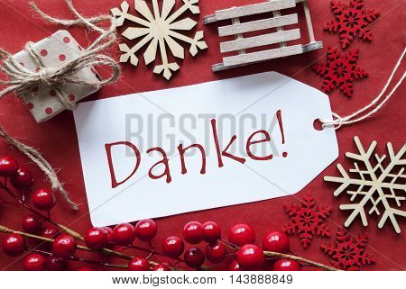 Christmas Decoration Like Gift Or Present, Sleigh. Card For Seasons Greetings With Red Paper Background. German Text Danke Means Thank You