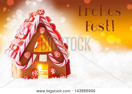 Gingerbread House In Snowy Scenery As Christmas Decoration. Candlelight For Romantic Atmosphere. Golden Background With Bokeh Effect. German Text Frohes Fest Means Merry Christmas