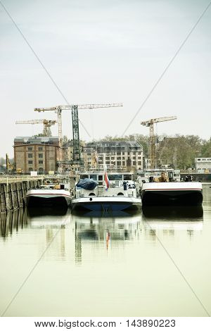The wine warehouse building in the Inland Port of Mainz with mirrored transport ships in the water.