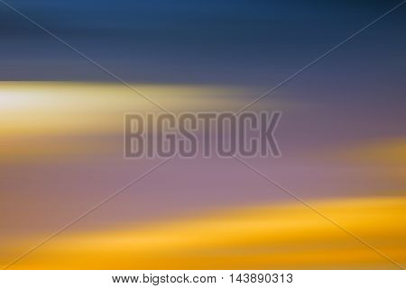 A blurred sky with different colored and colorful clouds.